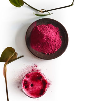 Beetroot latte on table next to beetroot powder